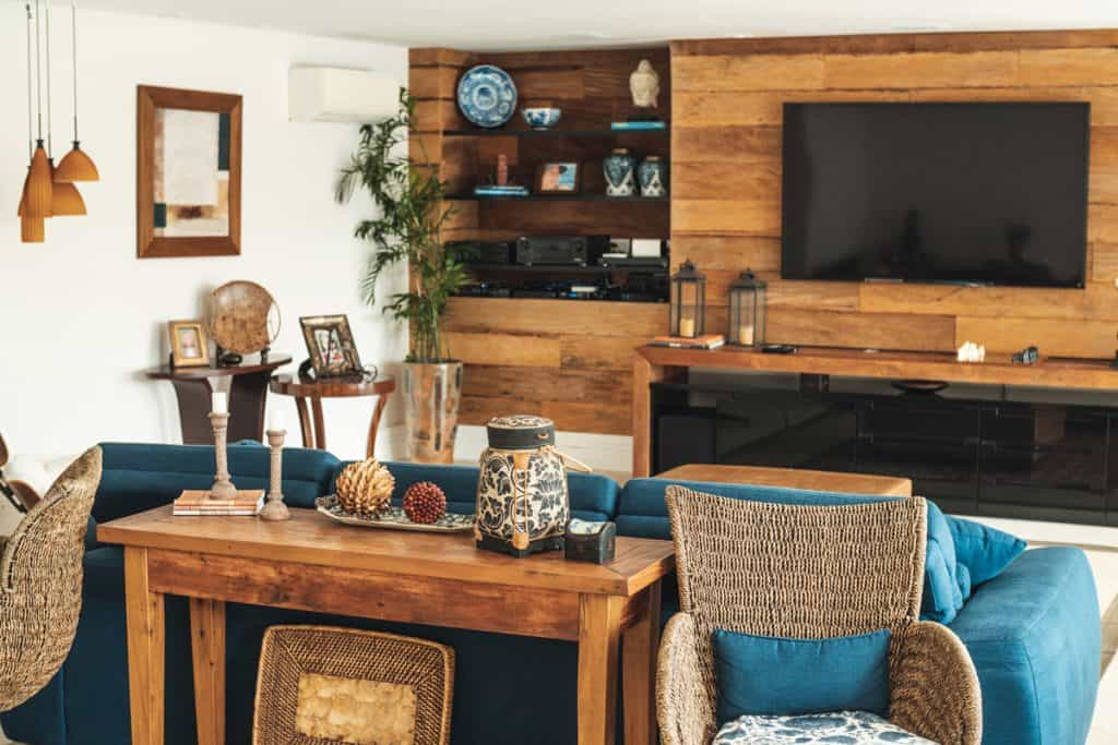 A rustic themed living room with wooden panels on the TV section and a blue couch in front