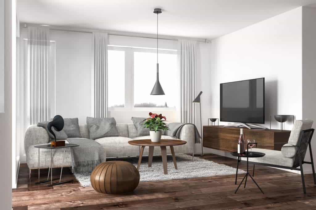 A white themed living room with a gray couch brown table, brown ottoman, and a brown TV cabinet