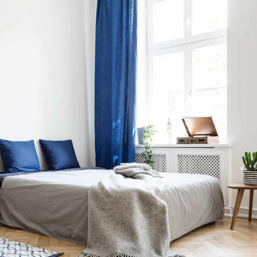 Bedroom design in modern apartment. Bed with dark blue pillows and grey duvet and blanket next to window.