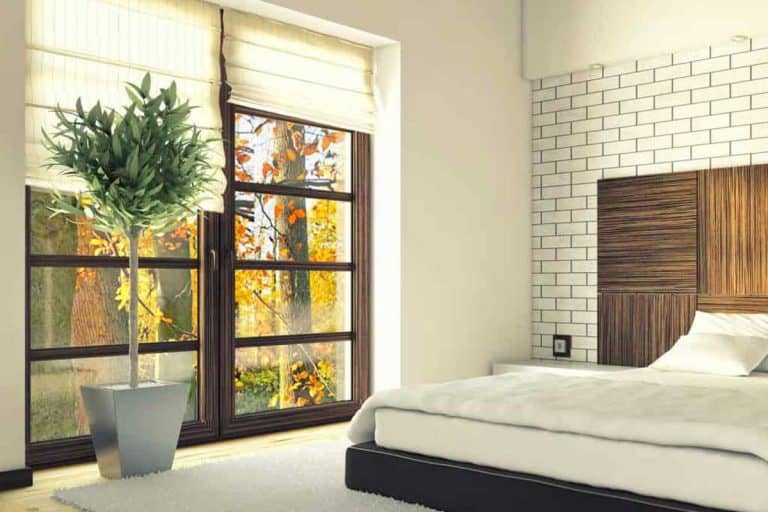 Bedroom with brick wall and large window with standing plant, 11 Bedroom Window Decor Ideas [With Pictures]