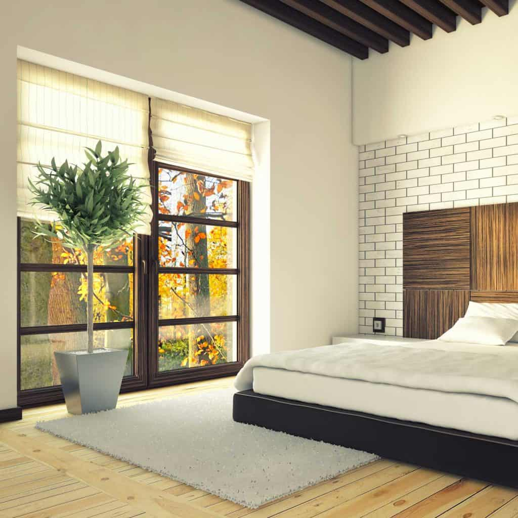 Bedroom with brick wall and large window with standing plant