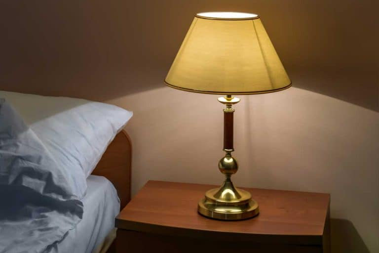 Classic lamp with turned on bulb under lampshade against wall in bedroom, Why Does My Lampshade Look Yellow? [And how to reverse the effect]