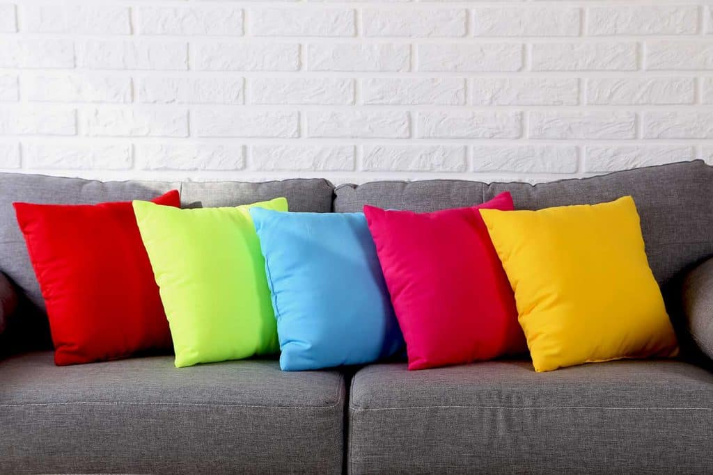 Colorful pillows on gray sofa on a brick wall background