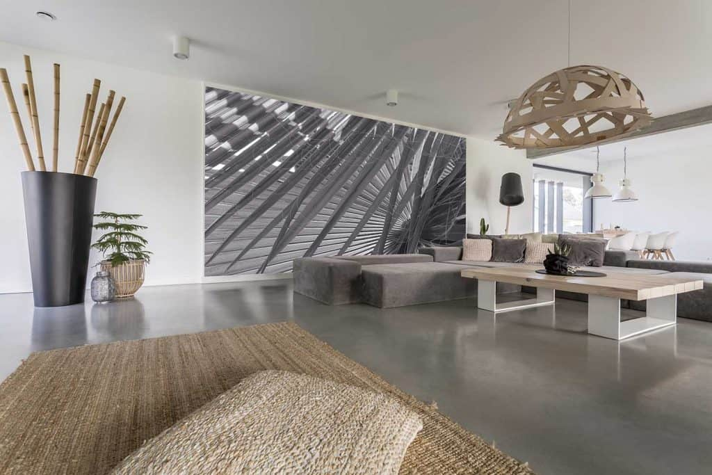 Decorative chandelier above designed table in living room with gray mural on wall