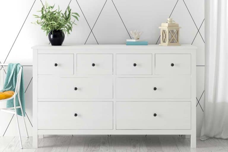 Dresser drawer in a white interior room with wooden floor, Should You Empty Dresser Drawers When Moving? [How to move a dresser safely]