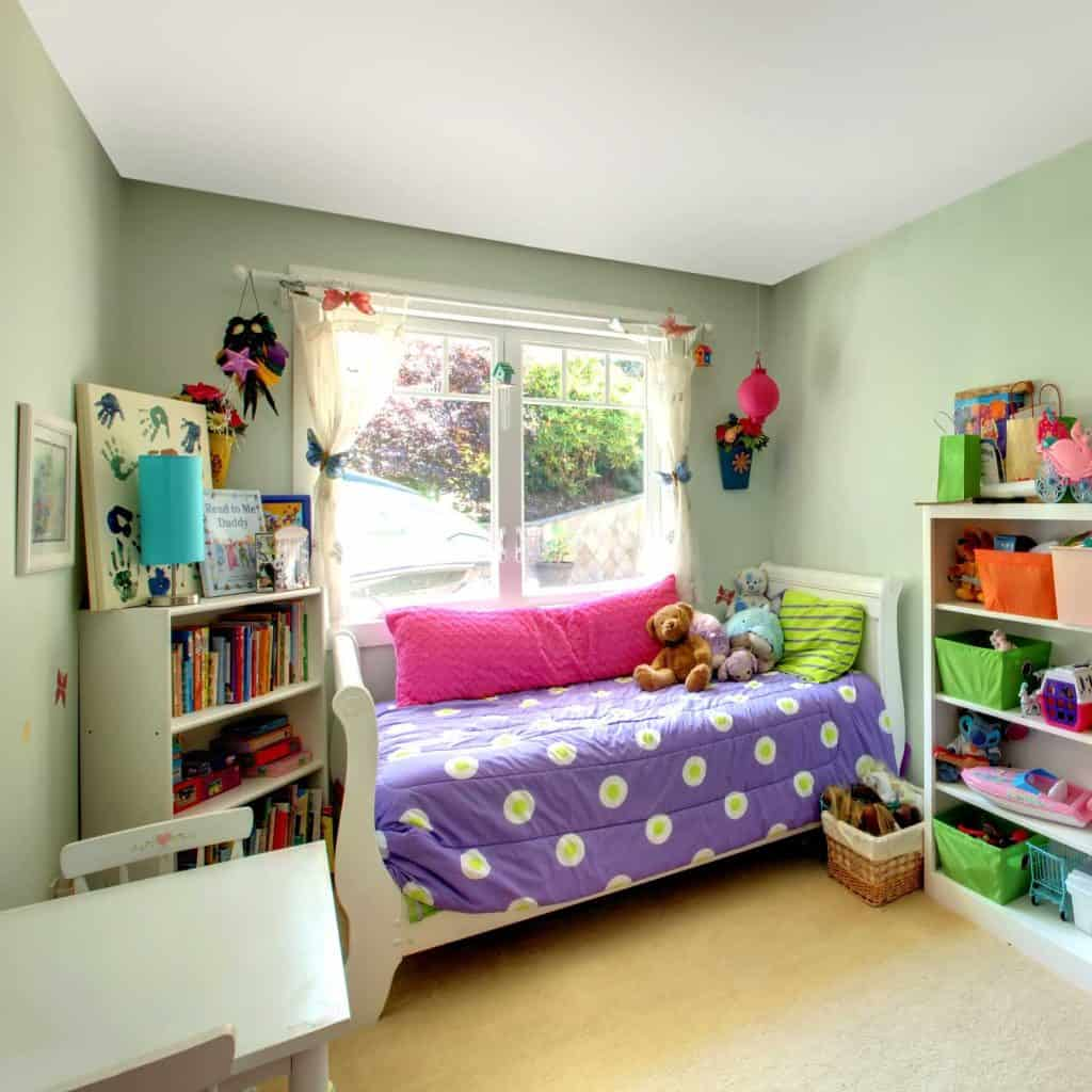 Girls bedroom with many toys and purple bed beside the window