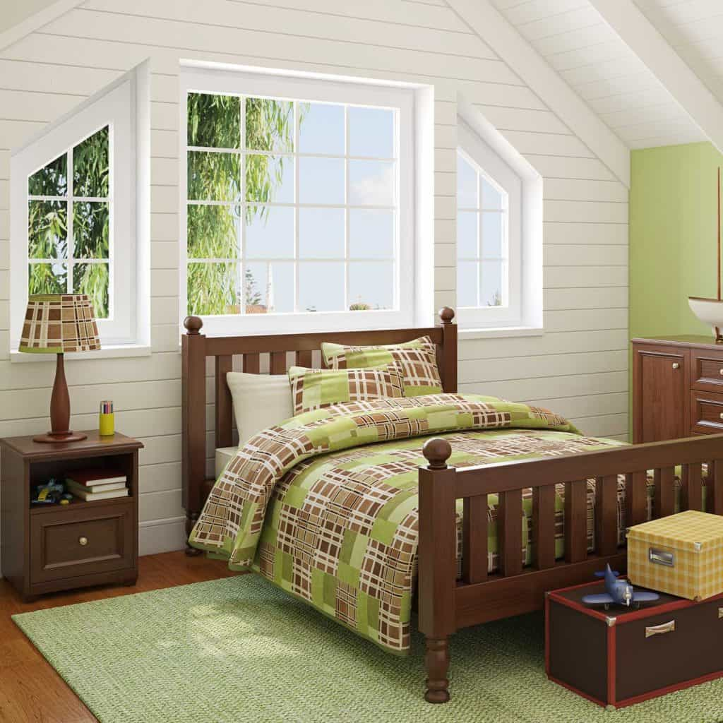 Green themed boys bedroom with wooden furniture and bed beside the window