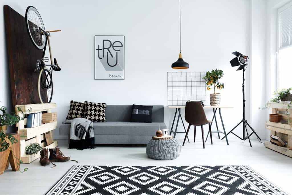 Hipster style white living room with sofa, pouf, carpet and bike on wall