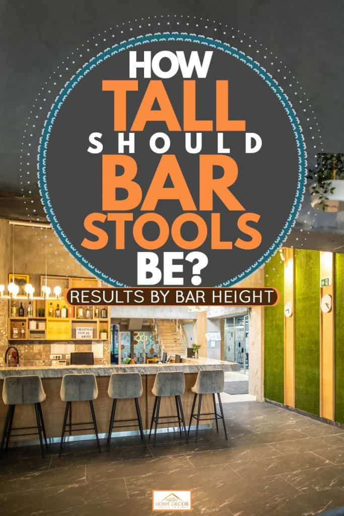 A modern bar with five bar stools and a grass textured decorative wall, How Tall Should Bar Stools Be? [Results by bar height]