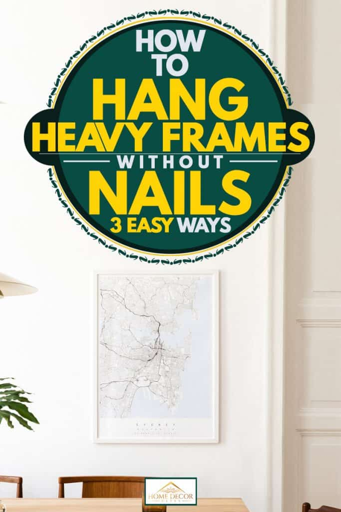 A modern dining room with a framed map hanging on a white wall, How To Hang Heavy Frames Without Nails [3 Easy Ways]