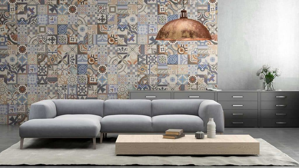 Interior with large blue vibrant sofa with coffee table, large pendant light above, tiles on the wall, with carpet, shelf and flowers
