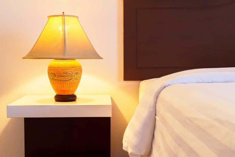 Lamp on a night table with light switched on beside the bed in a cozy bedroom, How To Decorate A Lampshade [Best 4 Suggestions]