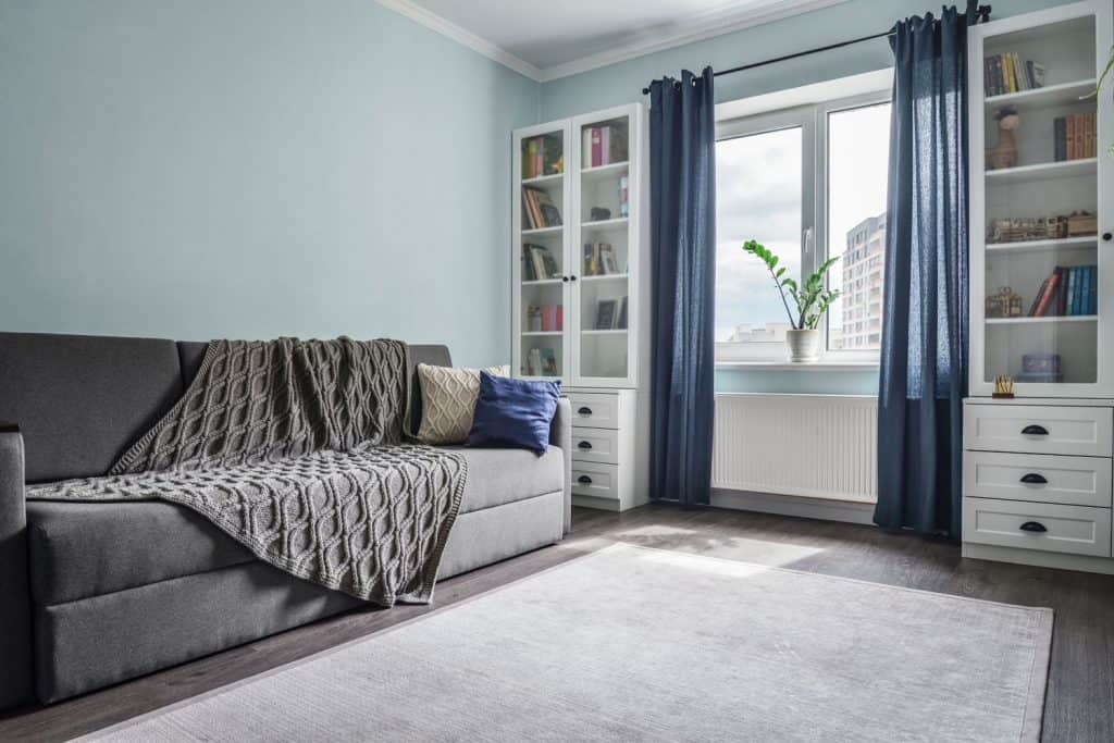 Light cozy teen room with white bookcases, grey sofa and blue wall