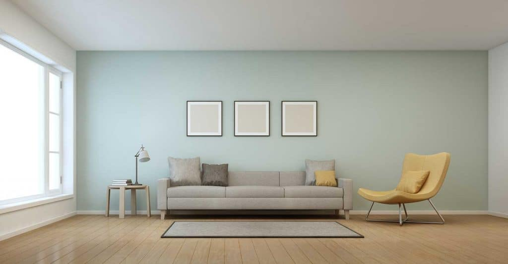 Living room in modern house with blank framed posters on wall