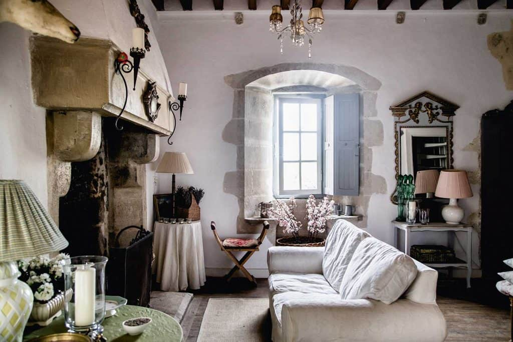 Living room interior in vintage French style with old chimney, wooden ceiling, chandelier, wall lamps and table lamp shades