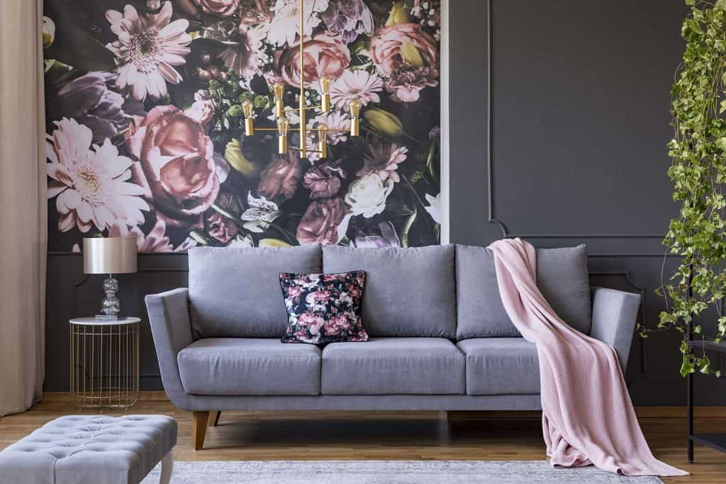 Living room interior with a sofa, pillow, blanket and flowers on wallpaper