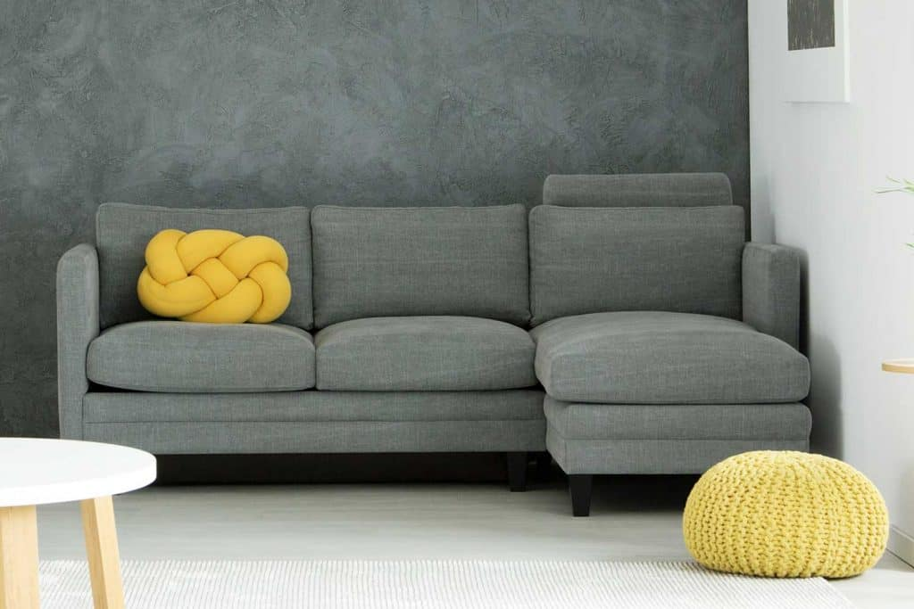 Living room interior with yellow pouf next to corner couch