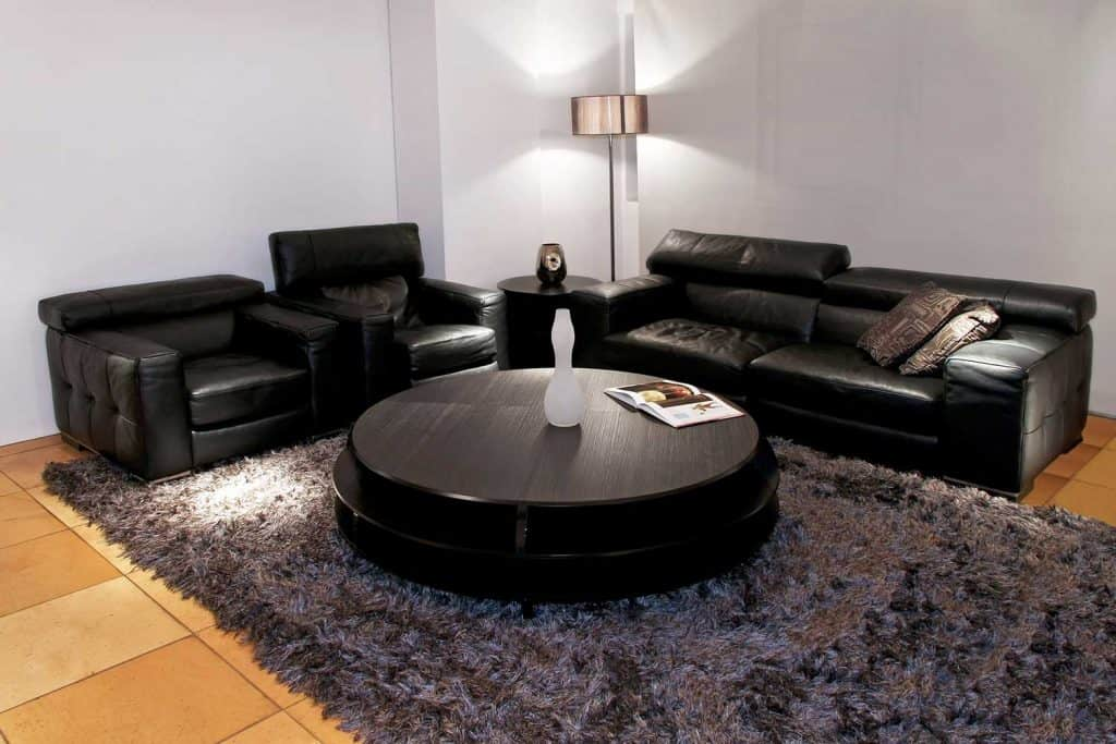 Living room with black leather sofa set, carpet and round coffee table