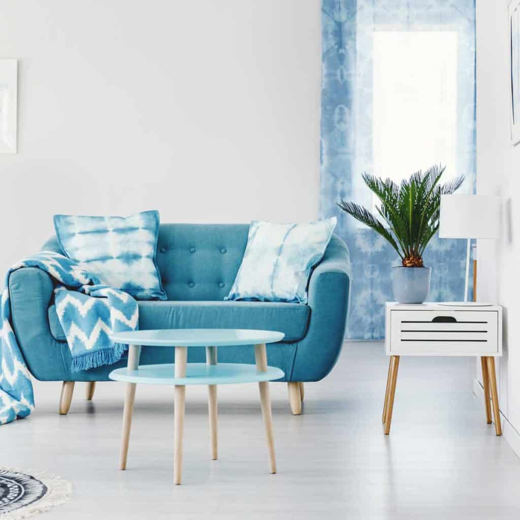 Metal shelves in turquoise apartment interior design with patterned blanket on settee near round table and plant on cabinet