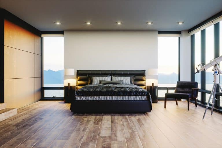 Modern bedroom with a panoramic view of the ocean visible with its huge windows paired with a luxurious dark themed bed and a concrete covered headboard, Do Beds Need a Headboard? [The answer may surprise you!]
