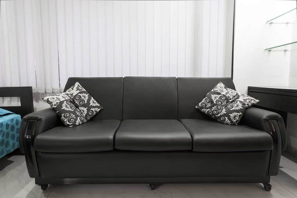 Modern black leather sofa in apartment with throw pillows