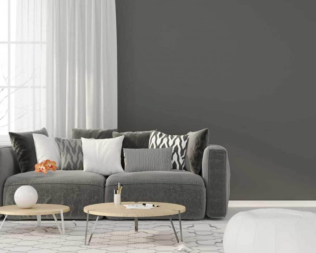 Modern interior living room with gray sofa, throw pillows, coffee table and gray wall