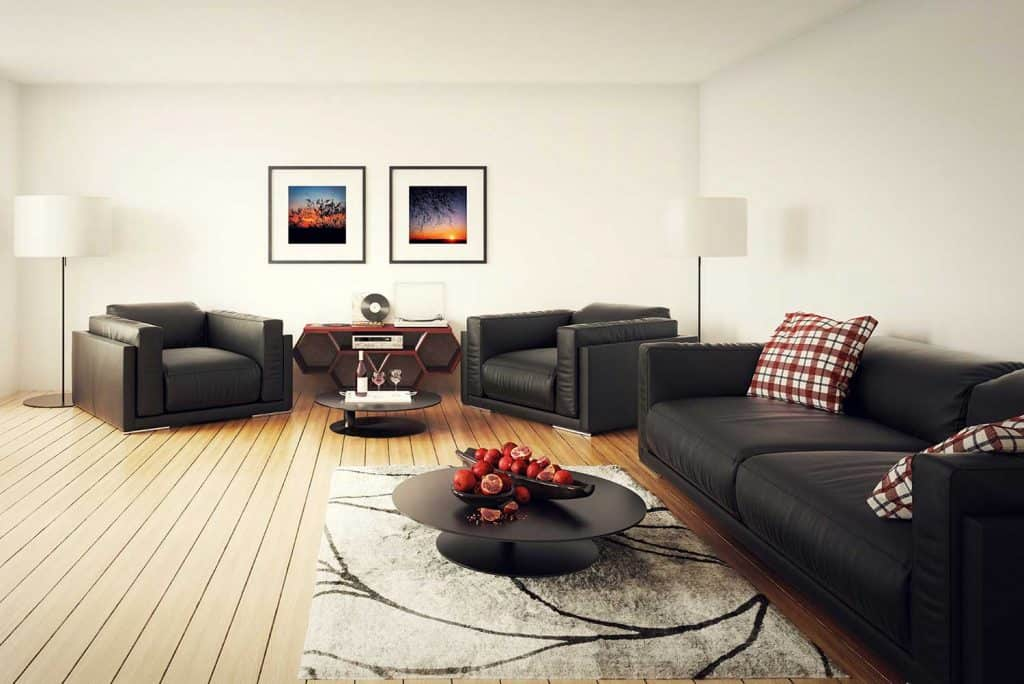 Modern living room with black leather sofa set, coffee table, carpet on hardwood floor and poster on wall