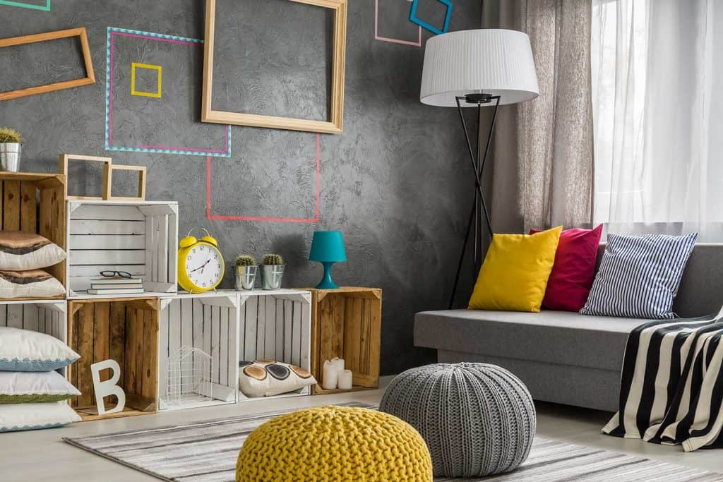 Modern style living room with gray wall, diy regale, sofa and poufs