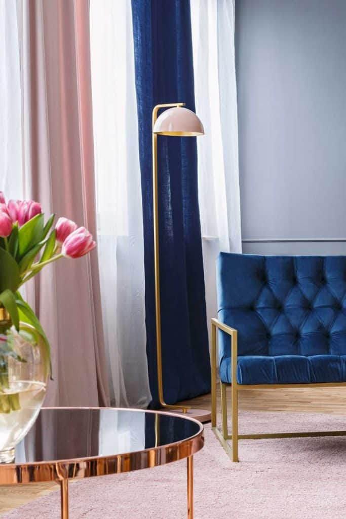 Navy blue armchair next to lamp in sophisticated apartment interior with painting and flowers