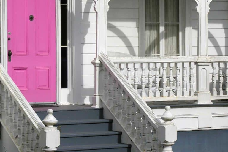 Pink exterior door on white Victorian house, 15 Types of Porches Every Homeowner Should Know