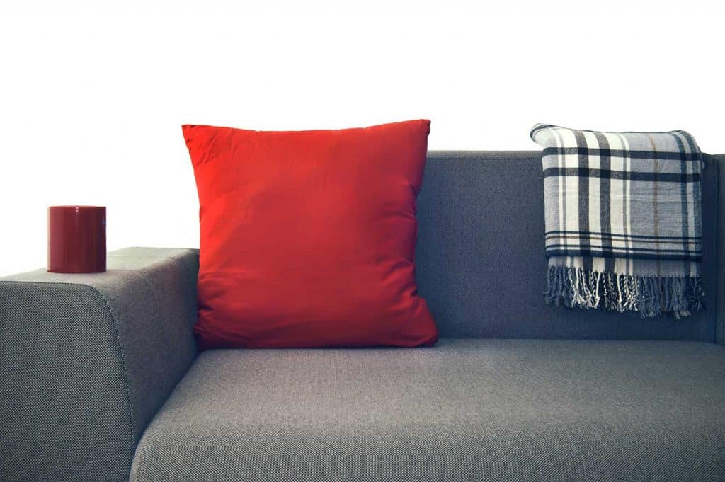 Red pillow on a gray couch