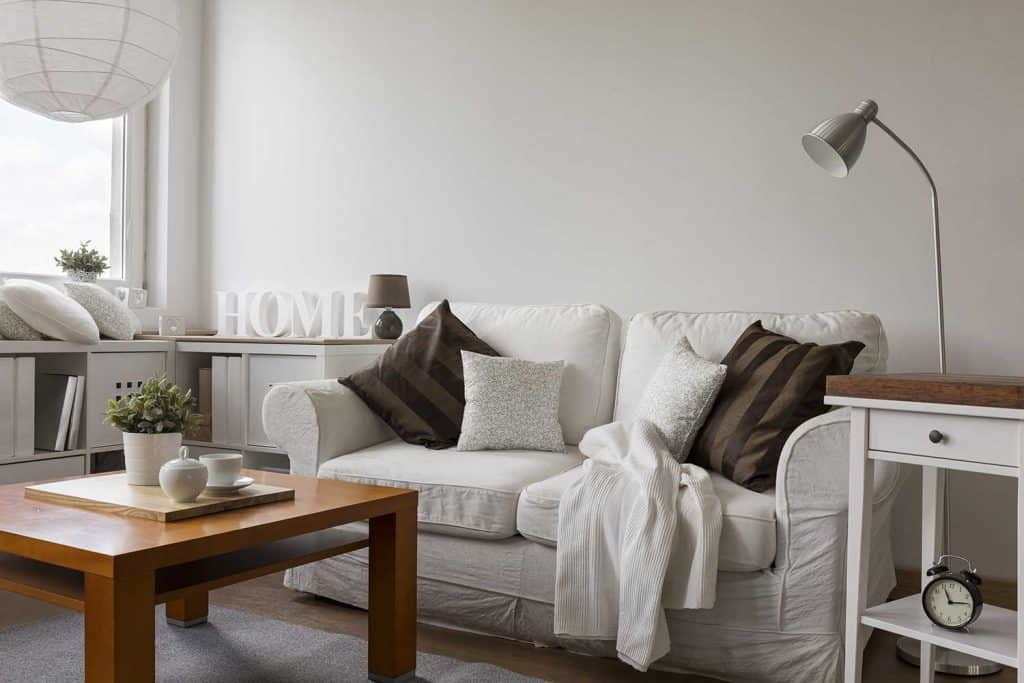 Small cozy living room with a tall metal floor lamp beside the white couch