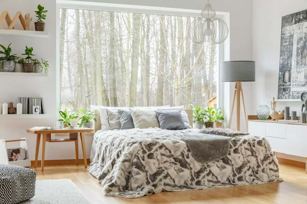 Spacious, cozy bedroom interior with a king-size bed with grey cushions, and large bedroom window