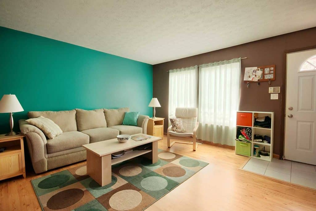 Teal and brown theme family room with matching two side table lamp shades
