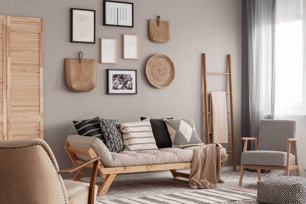 Trendy vintage armchair next to chic scandinavian sofa with pillows in classy living room interior with gray wall