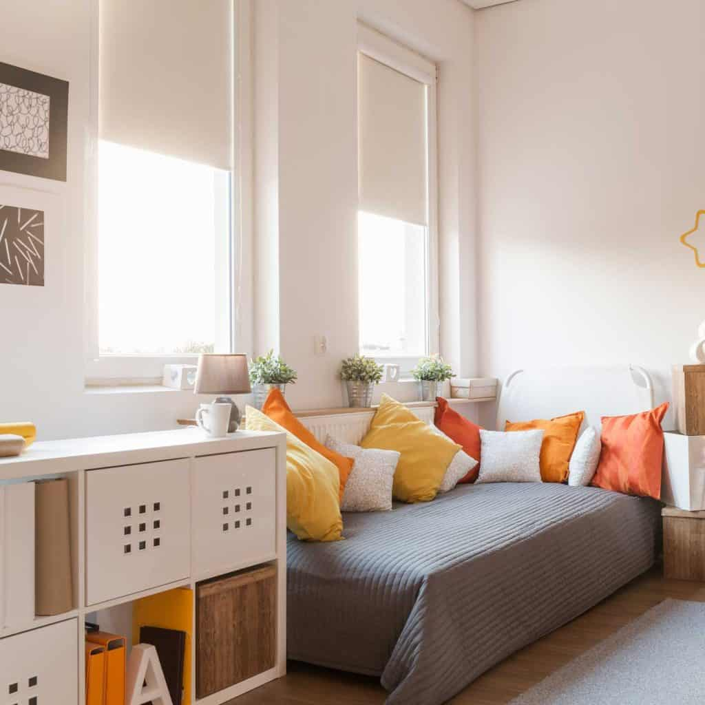 Yellow and orange themed bedroom with potted plants by the window