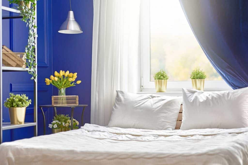 bedroom with navy blue curtain by the window