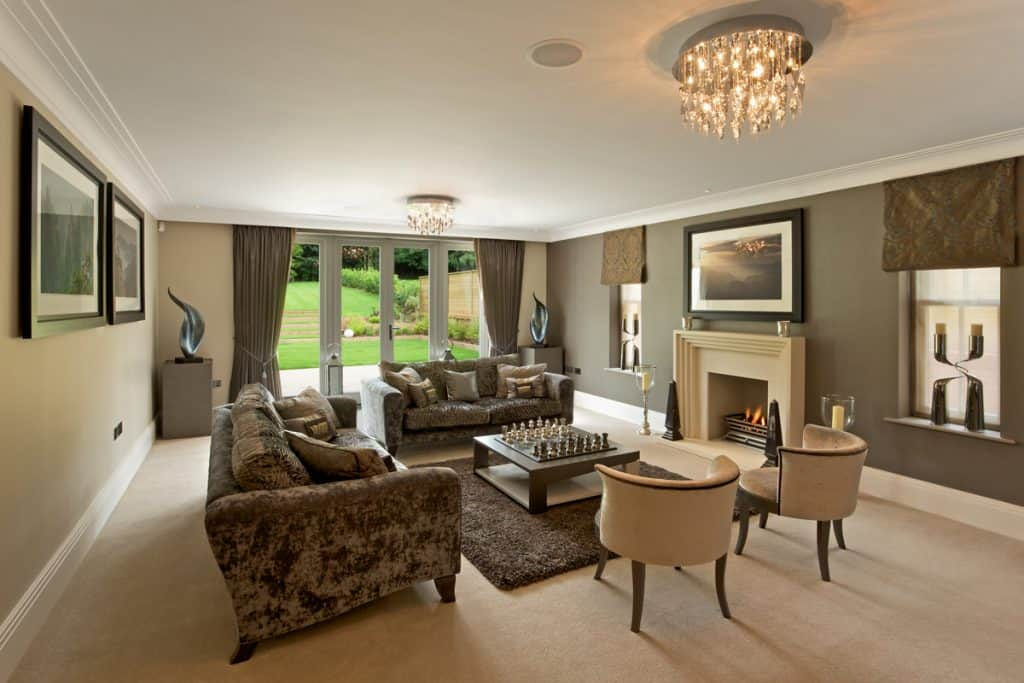 A brown themed living room incorporated with brown furnitures and a beige colored fireplace mantel