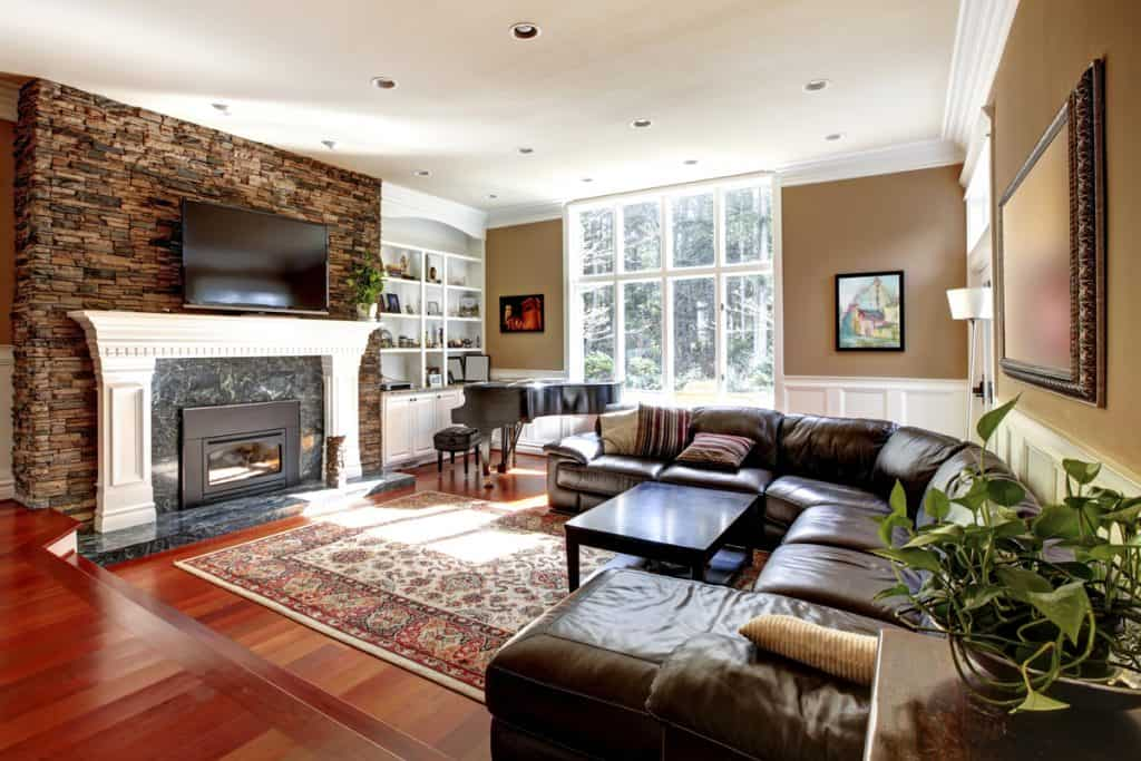 A brown themed living room with a fireplace decorated with stones on the walls and a brown couch
