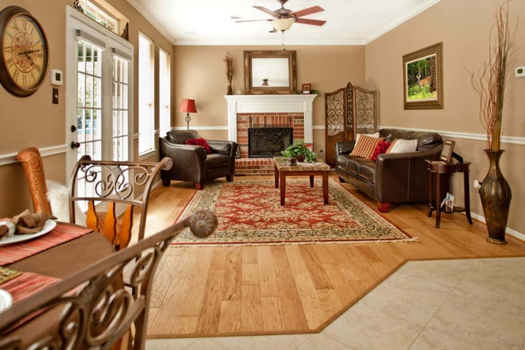 A brown themed living room with a wooden paneled flooring and walls consolidated with brown furnitures