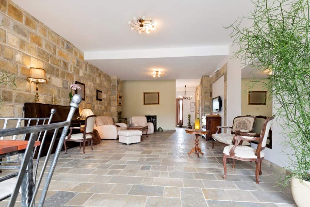 A classic themed house with stone decorated wall incorporated with white furnitures matched with a stone tiled floor