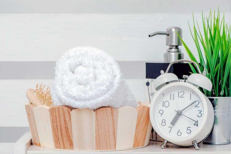 Bathroom with clean towel in a bucket, clock and hand sanitizer, Can You Put A Clock In The Bathroom? [Inc. Suggestions for Unusual Bathroom Clocks!]