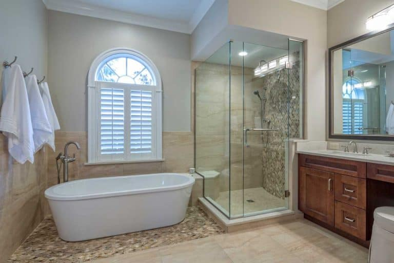 A complete remodeled master bathroom interior with hinged shower door