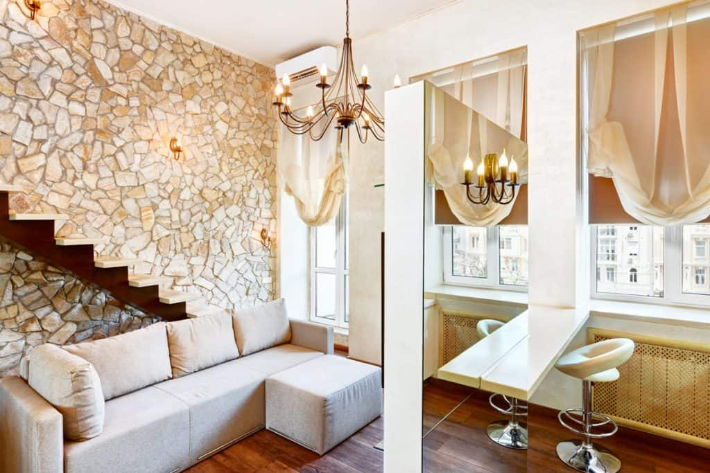 A cool modern themed room with a faux decorative wall on the side and huge mirror on the dressing area