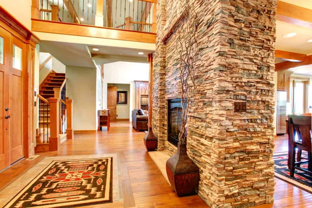 A decorative stone veneer in the fireplace section with wooden flooring