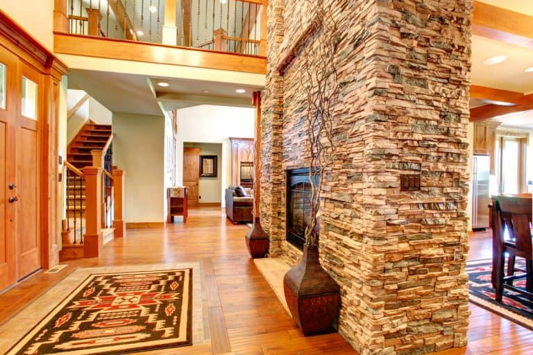 A decorative stone cover in the fireplace section with wooden flooring, Is Stone Veneer Worth It? Stone Interior Walls Pros and Cons