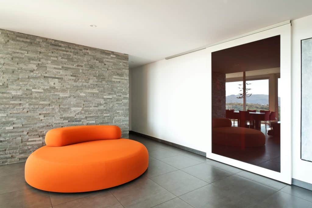 A gorgeous and spacious living area with a stone decorated veneer on the wall on the left side and a white wall on the corridor on the right