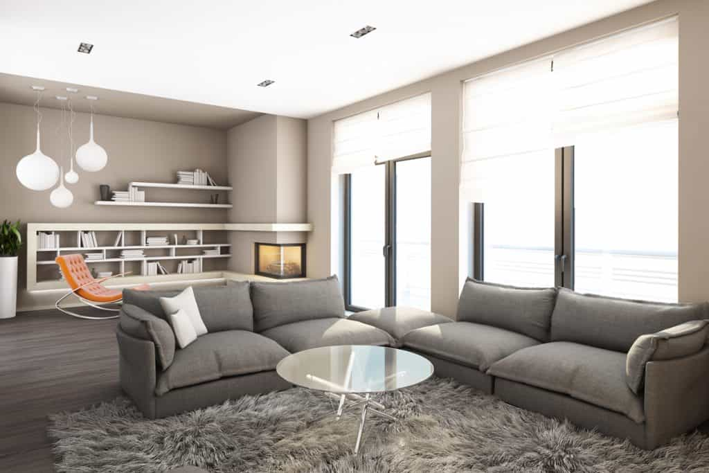 A gray themed living room with gray colored sofas rugs and sliding windows