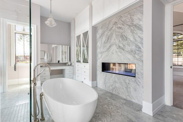 A luxurious living room with gray porcelain tiles and a big white bath tub, Is Porcelain Or Ceramic Tile Better For Showers? What homeowners need to know