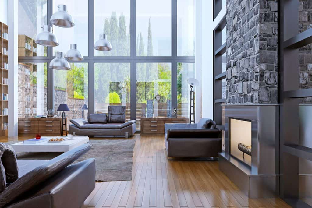 A luxurious living room with a huge steel framed window, wooden flooring and a faux decorated fireplace